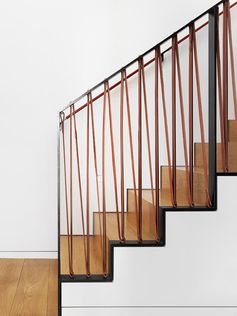 A stair railing made from black steel and soft saddle leather.