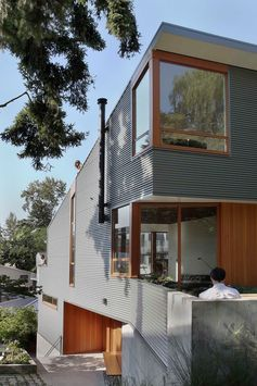 A house with corrugated metal siding and wood window frames.