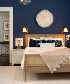 Sway Studio bedroom - Paint color is Stunning by Benjamin Moore, Serena & Lily Harbour Cane Bed, African Juju hat, Serena & Lily sconces, Serena & Lily Heath rug, gray bone inlay nightstands, buddha figurine, white moulding, white bedding, indigo pillows, camel throw