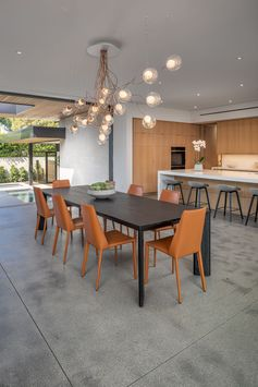 Dining Room Ideas - A dining table with a sculptural chandelier separates the living room and the kitchen, while polished concrete floors have used throughout this modern house. #DiningRoomIdeas #DiningRoom #SculpturalChandelier