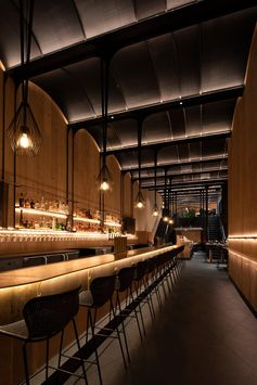 This modern restaurant has a high vaulted ceiling, wood walls, hidden lighting, an expansive bar, and various dining areas, including booth and banquette seating. #RestaurantInterior #ModernRestaurant #BarInterior #BarDesign