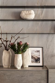 Shelving Ideas -Thin minimalist black shelving provides a contrasting element to the textured stone wall. #BlackShelving #ShelvingIdeas #Shelving