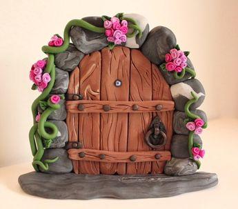 Woodland Fairy Door with Pink Flowers around a Wood Effect Door. Handmade using Polymer Clay