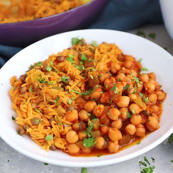 My mama's delicious vegetarian Puerto Rican inspired recipe: chickpeas in sofrito served with arroz con gandules (rice with pigeon peas). Delicious and packed with plant-based protein!