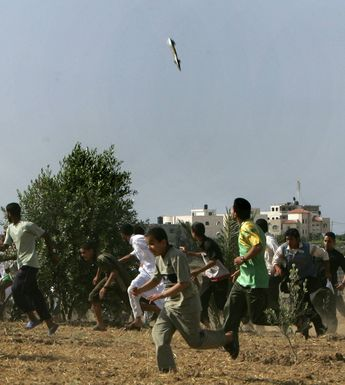 This is a 2008 Pulitzers prize winning picture of a missile, caught in mid-air, as it falls on a target in the Gaza Strip while young Palestinians scramble for safety [1880x2100] © Mahmud Hams.