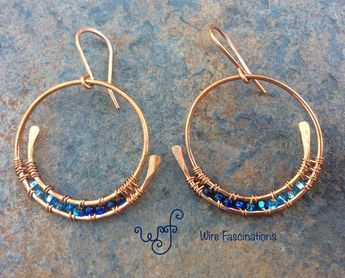 These handmade copper earrings are medium-large spiral hoops with wire wrapped blue crystal glass beads.