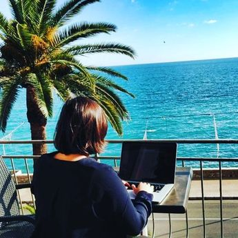 Our awesome designer @kasia.bul working with a view from Nice, France on this beautiful day! Where are you working from today?  #remotework #workfromanywhere #remote #workandtravel #officefortheday #france #nice #nomadpass #designer #office #outdooroffice