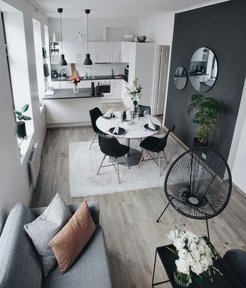 Scandinavian elements (1) simple silhouette of the sofa (2) Eames dowel chairs American but commonly used in Scandinavian style (3) white walls (4) area rug for warmth (5) bare windows for maximum lighting. Addition of Acapulco Chair, also a mid-century made piece, is a nice touch. Black touches in the right places. #scandi #blackandwhite