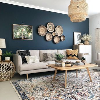A dark blue accent wall with cream sofa, wicker baskets used as art and a rug that compliments the scheme
