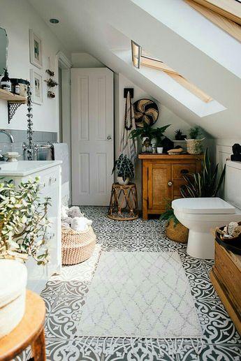 Une salle de bain cosy et végétale. On y trouve des meubles en bois massif qui lui confèrent beaucoup de caractère, un carrelage à motif géométrique absolument ravissant, un panier à linge en corde, des plantes pour la déco
