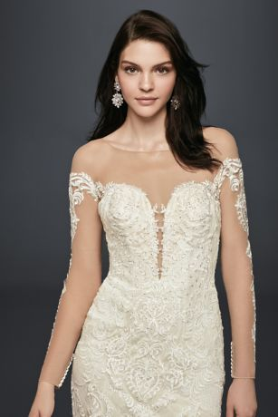 275a9f1ba0bd Crafted of appliqued lace and featuring a dramatic tiered train, this long  sleeve illusion gown