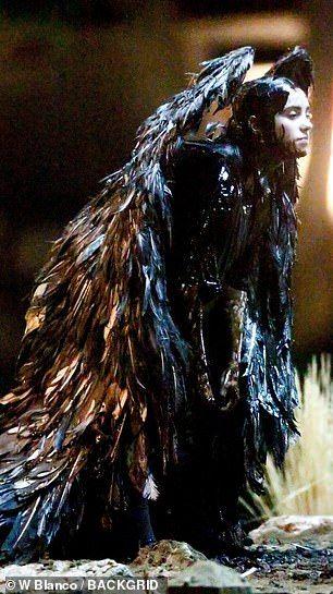 Billie Eilish is covered in black makeup while wearing angel wings