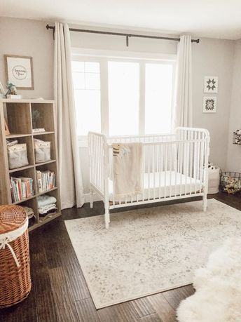A neutral nursery decorated with an ivory rug, a vintage-style crib, and lots of functional storage options. Rearranging Our Neutral Nursery – Valley + Birch #neutralnursery #nursery #nurseydecor #nurseryinspiration #nurseryideas #crib #farmhouserug