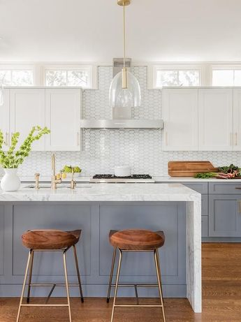 A set of low back oak wood island stools tucked under a white marble waterfall island makes for a stylish and comfortable place to enjoy a casual meal or hang with the cook during meal prep.