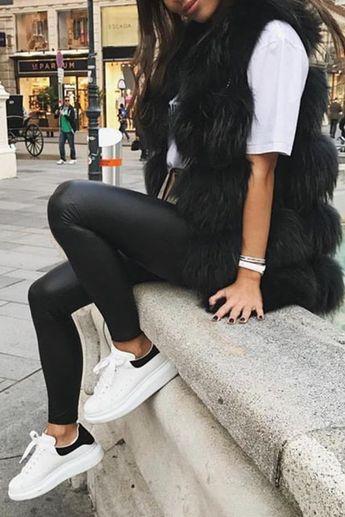 Mode femme automne avec un legging similicuir, des baskets Alexander Mcqueen, un large tshirt blanc et une veste fourrure sans manches
