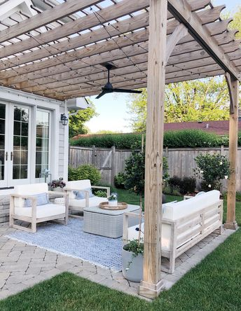 Pretty outdoor space features pergola and paved patio, pottery barn outdoor rug, world market outdoor furniture, and pretty outdoor pillows. #outdoordecor #patiofurniture #patiodesign #patio