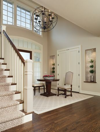 Gorgeous foyer with center table. Niches are lined with mother-of-pearl wallcovering. The 48 inch chandelier was custom made. Interior by Amy Weinstein.