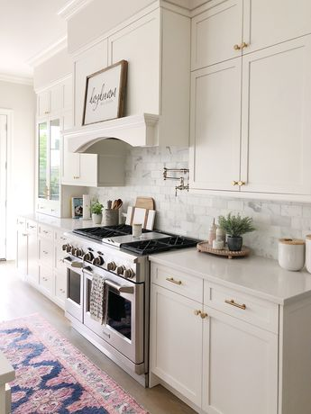 White kitchen cabinets with marble subway backsplash, features bright runner and pretty kitchen decor #kitchendesign #kitchenideas #kitchenremodel #decoratingideas
