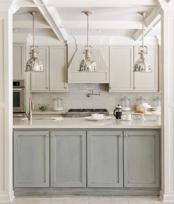 Fabulous two-tone kitchen design with ivory off-white shaker kitchen cabinets, gray green faux finish kitchen island, silestone quartz counter tops, Walker Zanger glossy subway tiles backspalsh, pot filler, polished nickel industrial yoke pendants and coffered ceiling.