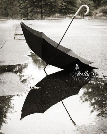 Black umbrella reflected in a puddle on a rainy day. Gives me a melancholy…