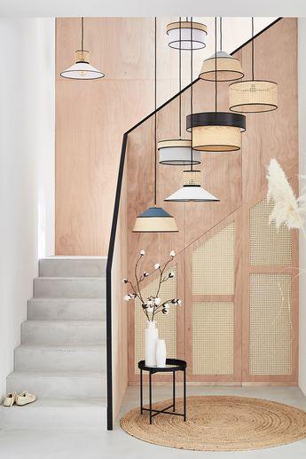 Profitez de la verticalité de la cage d'escalier en y installant une accumulation de luminaires. Les suspensions sont mises en valeur par des matières naturelles : le cannage et le raphia créent une ambiance chaleureuse complétée par un liseré noir qui souligne la rampe d'escalier. Avec cette idée déco, votre entrée est joliment mise en avant !