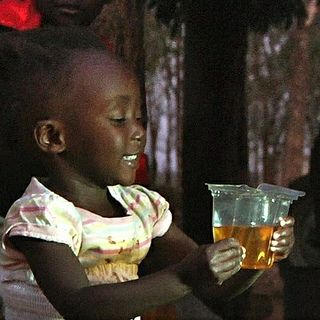 Child drinking ORS from Kit Yamoyo (square) by ColaLife, via Flickr