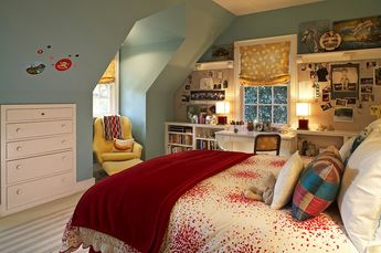 Fun, colorful girl's bedroom! Blue gray paint color, yellow tufted chair & ottoman, silk gold roman shade, white & red bedding, bookcases, desk, and striped rug.