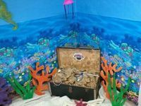 Coral Reef Room,Amazing Wonders Aviation .Very Simple. Find an old trunk, stuff it with brown paper, top with little girl's jewelry and gold coins and you have a treasure chest! Background, coral reef is from Party City,$7.99, topped with blue paper from Ed.Wonderland, reefs can be made from cardboard, but we had foam board from last year's VBS and just paint! We placed a tan sheet on floor for sand. Kids loved it!