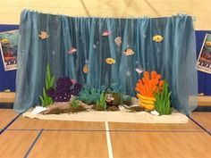 This is the Great Barrier Reef that I created for AWA 2012. I draped tarps and fabric over giant sheets of cardboard for the water and used a painter's tarp for sand.  The coral and seaweed were cut from styrofoam.
