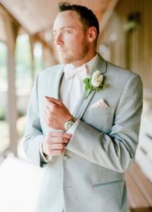 Such a handsome groom in a light gray suit, light blush pink bow tie and boutonniere.  Seriously handsome! Taken at THE SPRINGS Event Venue in Edmond, OK.  Book your free tour today! Groom attire, handsome groom attire, light gray groom's attire, blush wedding groom suit