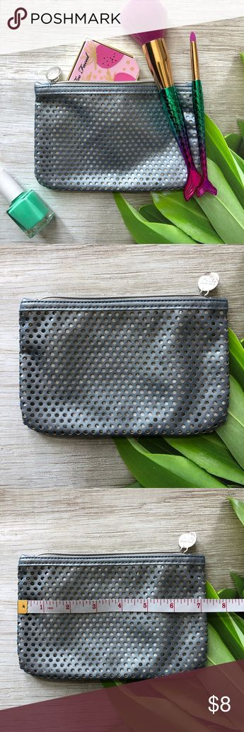NWOT silver perforated Makeup bag NWOT Cute makeup bag that has room to hold plenty of your everyday essentials. Bag has an outer shell that is silver and perforated, giving it a little bit more interest and texture.  Has a lighter silver  inner lining and a zip enclosure.   Perfect to use as a gift bag for the upcoming holidays or that little gift for someone.   Please ask questions and happy poshing Bags Cosmetic Bags & Cases
