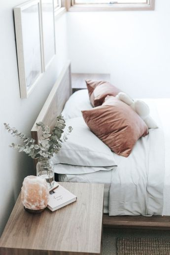 crushed velvet dusty rose pillow covers, salt lamp, eucalyptus on nightstand, simple book, morning light from the window
