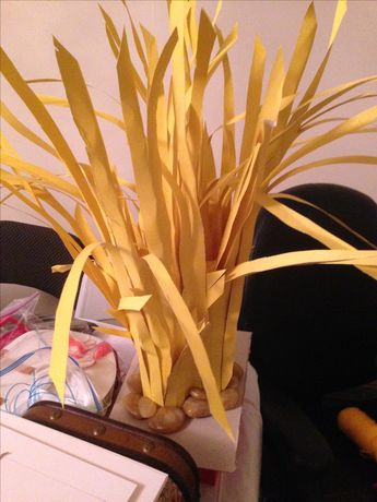 Savannah grass. 3 pool noodles hot glued to a piece of cardboard. Yellow poster board is cut into strips and glued in to the pool noodles: