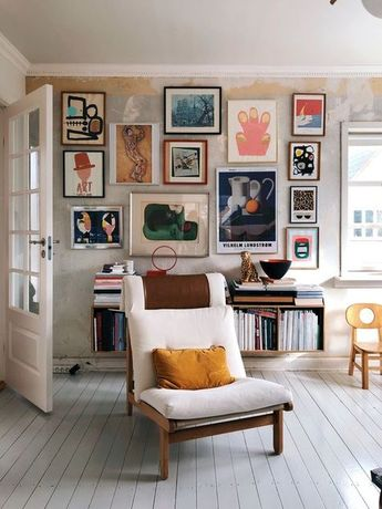 The bright colors inside the picture frames stand out against the white walls.