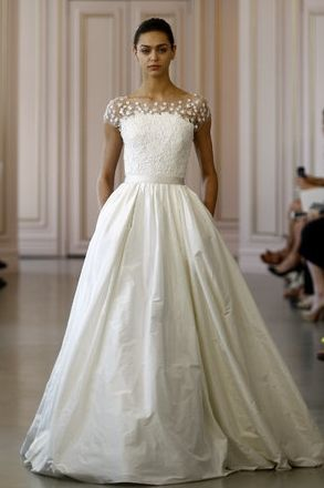 At Oscar de la Renta, an illusion top that makes it appear as though white flowers are scattered across the bride's collarbones and shoulders. Coy and flirtatious.