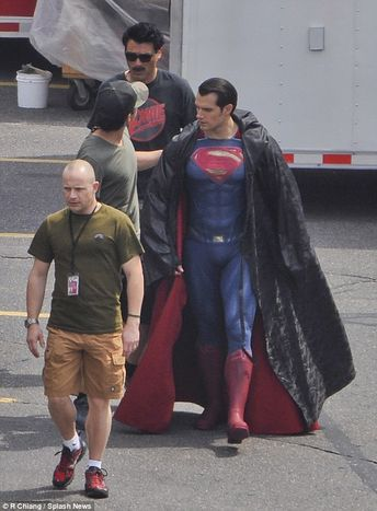 Henry Cavill shows off his muscles in superhero costume on the set