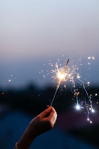 Woman's hand holding sparkler to the sky at twilight by Saptak Ganguly for Stocksy United