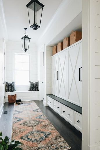 Long cottage mudroom boasts seeded glass carriage lanterns above an orange and blue runner layered over dark stained wood floors.