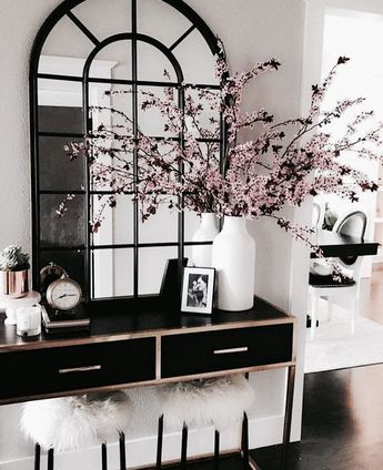 A chic BLACK & WHITE foyer.  The Renaissance-inspired mirror, the gold trimming & the fur upholstery on the stool - they all make this space look sophisticated.  The flowers add some welcomed  color &  texture. #blackandwhite #interiordesign