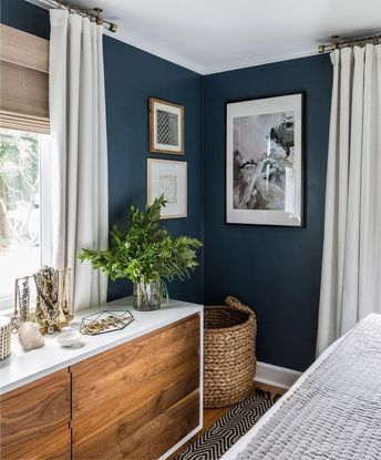 Master Bedroom decor- love the cosy navy wall with airy white curtains. Add some timeless pictures, neutral wood and a pop of plant for freshness