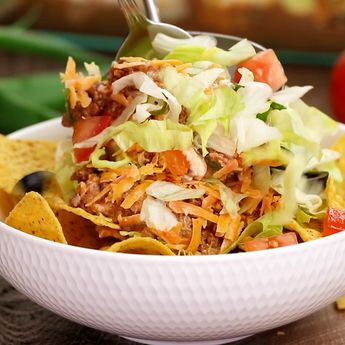 Go big with this layer taco dip recipe - it is the perfect appetizer for large crowds. It's full of meat, cheese, veggies and more! Remove or add layers to please everyone! #game day #football #ideas |#foracrowd #party #food #tailgating #superbowl #easy #classic #best
