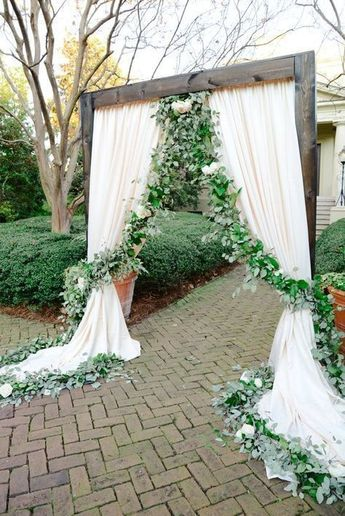 30+ Greenery Wedding Ideas That Are Actually Gorgeous---outdoor wedding arch with white drapery and greenery decors, spring and fall garden wedding theme