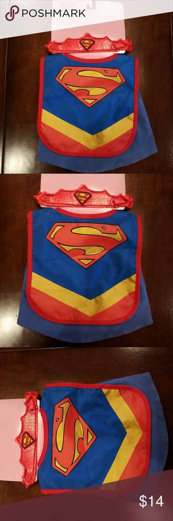 "NWT.  Supergirl Infant Caped Bib & Headband Set New with tags. Supergirl Caped Bib & Headband Infant Accessory Set.  Retail: $20  Adorably cute! DC Comics licensed. Great for Halloween or everyday use. Note: The package says ""Supergirl"" because it comes with a tiara headband, but it could be used as a Superman cape as it's the identical emblem & coloring.  Comfy and cute for baby. It has a bib featuring the Supergirl emblem on the front, an attached cape on back, plus an elastic tiara headband."