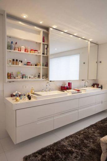 Banheiro suíte: armário suspenso, Cuba dupla (porém de apoio), bancada de mármore ou porcelanato que imita calacata ou Carrara.