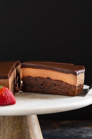 This triple Nutella mousse cake features a rich Nutella brownie base topped with a layer of luscious Nutella mousse filling and a layer of soft Nutella ganache. #bakedbyanintrovertrecipes #nutella #mousse #cake #baking #dessert #recipe