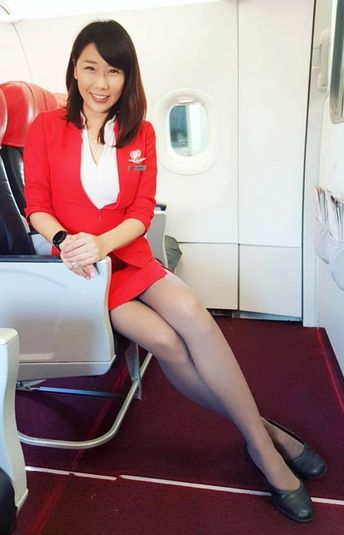 Asian Female Flight Attendant in red dress