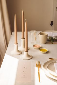 Natural and light stoneware golden Cutipol cutlery Ikebana flower arrangement with Daucus stoneware cups minimal glassware stoneware candle holder taupe tapered candles. white cotton linen napkin with vertical name cards on whitewashed wooden table. Menu on leather feel paper. Wedding table design inspiration by Hilde.