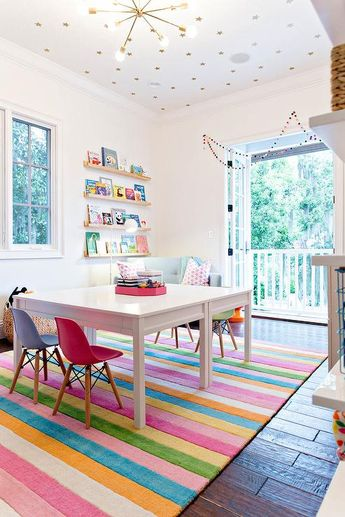 Colorful Eames Molded Plastic Mini Chairs sit on either side of a square white play table placed on a multi-colored striped rug illuminated by a brass sputnik chandelier fixed to a ceiling covered in Coronata Star Wallpaper.