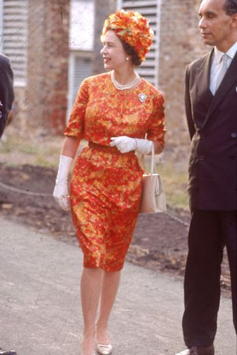Queen Elizabeth II, wearing an orange dress and tan pumps, arrives at Antigua in 1966.