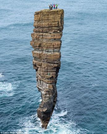 Daredevil climbers pick their way up perilous stack of rocks